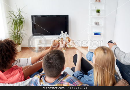 friends clinking beer and watching tv at home stock photo, friendship, drink, alcohol, holidays and people concept - happy friends clinking beer bottles and watching tv at home by Syda Productions