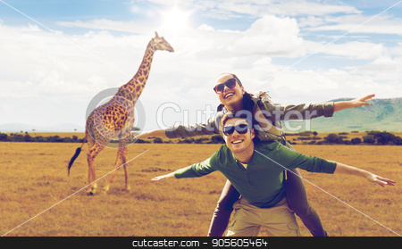 happy couple with backpacks having fun in africa stock photo, travel, tourism and people concept - happy couple with backpacks having fun over giraffe in african savannah background by Syda Productions