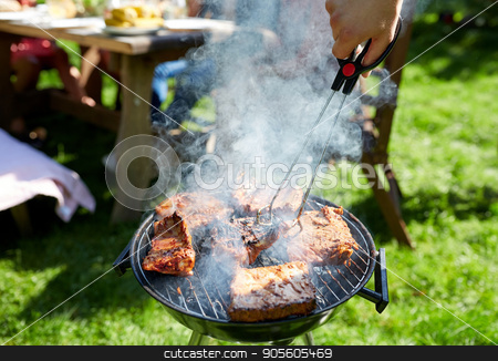 man cooking meat on barbecue grill at summer party stock photo, leisure, food, people and holidays concept - man cooking meat on barbecue grill for his friends at summer outdoor party by Syda Productions