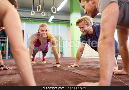group of people doing straight arm plank in gym stock photo, fitness, sport, exercising, training and healthy lifestyle concept - group of people doing straight arm plank in gym by Syda Productions