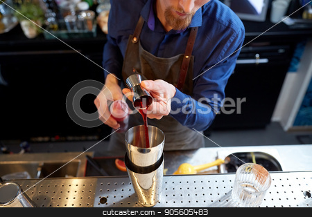 bartender with shaker preparing cocktail at bar stock photo, drinks, people and luxury concept - bartender pouring alcohol from jigger into shaker and preparing cocktail at bar by Syda Productions