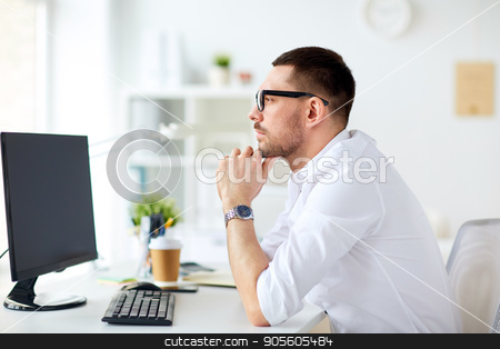 businessman in glasses sitting at office computer stock photo, business, people and technology concept - businessman in glasses sitting at office computer and thinking by Syda Productions