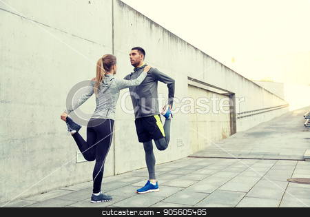 couple of sportsmen stretching leg on city street stock photo, fitness, sport, training and lifestyle concept - couple of sportsmen stretching leg on city street by Syda Productions
