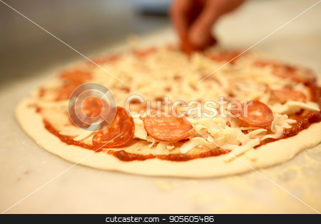 cook hands adding salami to pizza at pizzeria stock photo, food, culinary, italian cuisine, people and cooking concept - cook hands adding salami slices to pizza at pizzeria by Syda Productions