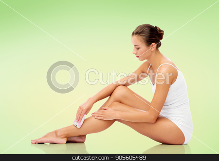 woman with epilator removing hair on legs stock photo, people, beauty and bodycare concept - beautiful woman with epilator removing hair from legs sitting on floor over green background by Syda Productions