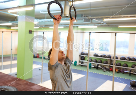 man exercising and doing ring pull-ups in gym stock photo, sport, fitness, training and people concept - man exercising and doing ring pull-ups in gym by Syda Productions