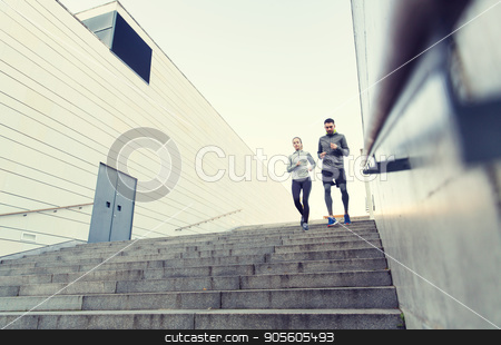 couple running downstairs on city stairs stock photo, fitness, sport, people, exercising and lifestyle concept - couple running downstairs on city stairs by Syda Productions