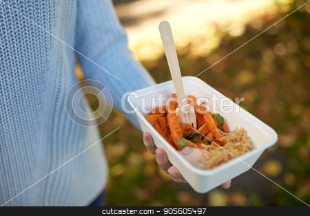 close up of hand holding plate with sweet potato stock photo, fast food, people and unhealthy eating concept - close up of hand holding disposable plate with sweet potato and fork by Syda Productions