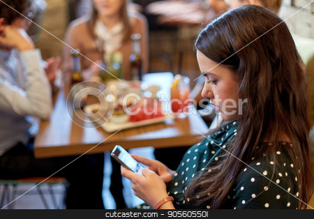 woman with smartphone and friends at restaurant stock photo, technology, lifestyle, holidays and people concept - woman with smartphone and friends at restaurant by Syda Productions
