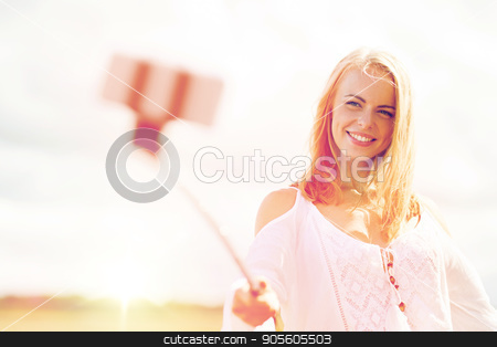 happy young woman taking selfie by smartphone stock photo, technology, summer holidays, vacation and people concept - smiling young woman in white dress taking picture by smartphone selfie stick on cereal field by Syda Productions