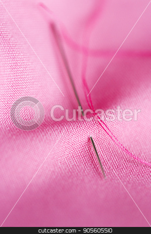 sewing needle with thread stuck into pink fabric stock photo, needlework and tailoring concept - sewing needle with thread stuck into pink fabric by Syda Productions