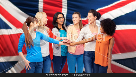 united nternational women over british flag stock photo, diversity, ethnicity and people concept - international group of happy smiling different women holding hands together over british flag background by Syda Productions