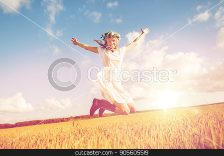 happy woman in wreath jumping on cereal field stock photo, happiness, nature, summer holidays, vacation and people concept - smiling young woman in wreath of flowers and gumboots jumping on cereal field by Syda Productions