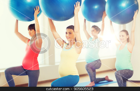 happy pregnant women exercising with ball in gym stock photo, pregnancy, sport, fitness, people and healthy lifestyle concept - group of happy pregnant women exercising with ball in gym by Syda Productions