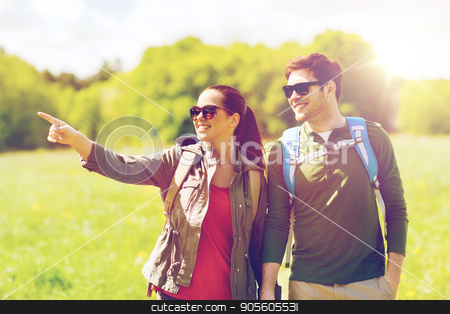 happy couple with backpacks hiking outdoors stock photo, travel, hiking, backpacking, tourism and people concept - happy couple with backpacks walking outdoors and pointing finger to something by Syda Productions