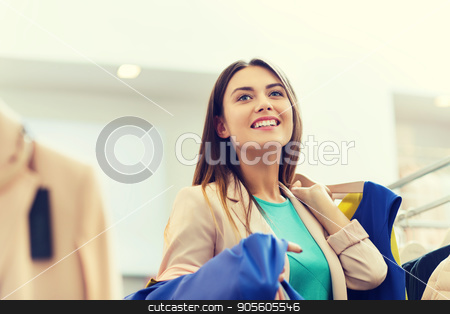 happy young woman choosing clothes in mall stock photo, sale, shopping, fashion, style and people concept - happy young woman choosing clothes in mall or clothing store by Syda Productions
