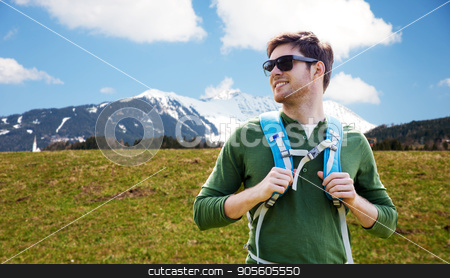 happy young man with backpack traveling stock photo, travel, tourism and people concept - happy young man in sunglasses with backpack over mountains background by Syda Productions