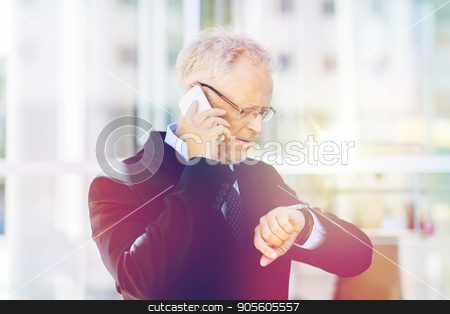 senior businessman calling on smartphone in city stock photo, business, technology, time, punctuality and people concept - senior businessman calling on smartphone an looking at wristwatch in city by Syda Productions