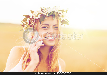 happy young woman calling on smartphone at country stock photo, summer holidays, vacation, technology and people concept - close up of smiling young woman in wreath of flowers calling on smartphone at countryside by Syda Productions