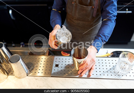 bartender with ice and shaker at cocktail bar stock photo, alcohol drinks, people and luxury concept - bartender adding ice into shaker preparing cocktail at bar by Syda Productions