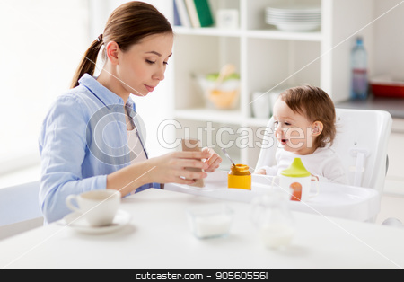 mother with smartphone and baby eating at home  stock photo, family, breakfast, eating, technology and people concept - happy mother with smartphone and coffee and little baby sitting in highchair at home kitchen by Syda Productions