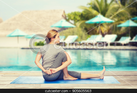 woman making yoga in twist pose on mat stock photo, fitness, sport, people and healthy lifestyle concept - woman making yoga in twist pose on mat over beach and swimming pool background by Syda Productions