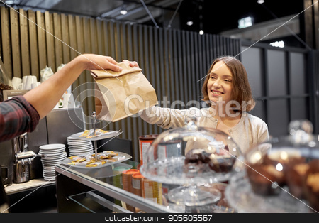 woman taking paper bag from seller at cafe stock photo, small business, takeaway food, people and service concept - happy female customer taking paper bag from man or barman at vegan cafe by Syda Productions