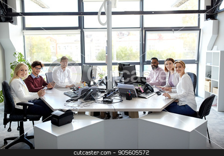 business team with computers working at office stock photo, corporate, technology and people concept - business team with smartphones and computers working at office by Syda Productions