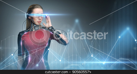 woman in virtual reality glasses and microchip stock photo, augmented reality, technology, business, future and people concept - woman in virtual glasses and microchip implant or sensors looking at diagram chart projection by Syda Productions