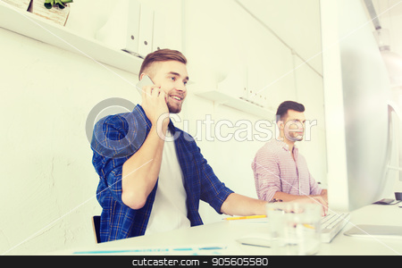 happy creative man calling on cellphone at office stock photo, business, technology, education and people concept - happy young creative man or student with computer at office calling on smartphone by Syda Productions