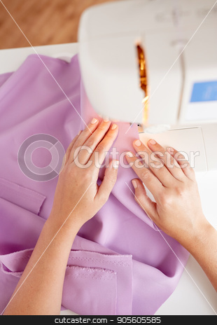 tailor woman with sewing machine stitching fabric stock photo, people, needlework and tailoring concept - tailor woman with sewing machine stitching fabric at studio by Syda Productions