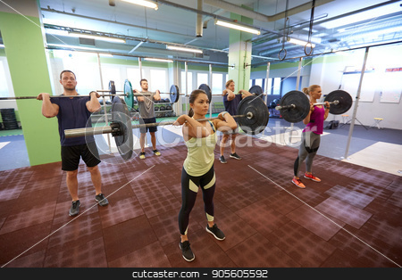 group of people training with barbells in gym stock photo, fitness, sport, training, exercising and lifestyle concept - group of people with barbells doing standing shoulder press in gym by Syda Productions
