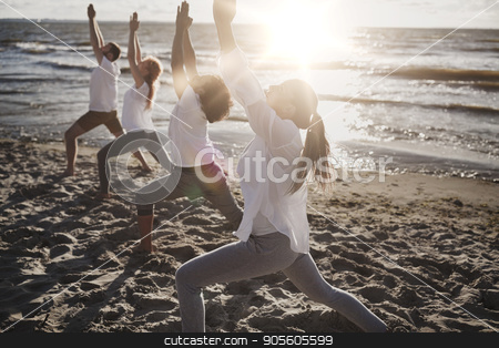 group of people making yoga exercises on beach stock photo, fitness, sport, yoga and healthy lifestyle concept - group of people making high lunge or crescent pose on beach by Syda Productions