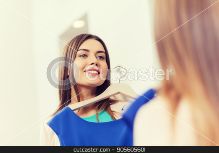 happy woman with clothes at clothing store mirror stock photo, shopping, fashion, style and people concept - happy woman choosing clothes and looking to mirror in mall or clothing store by Syda Productions