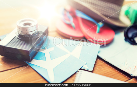 close up of camera, tickets and travel stuff stock photo, summer vacation, travel, tourism  and objects concept - close up of camera, airplane tickets and personal accessories by Syda Productions