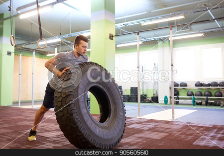 man doing strongman tire flip training in gym stock photo, strongman, bodybuilding, sport, fitness and people concept - young man doing tire flip at training in gym by Syda Productions