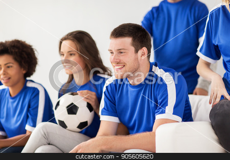 friends or football fans watching soccer at home stock photo, friendship, leisure, sport and entertainment concept - happy friends or football fans with ball watching soccer at home by Syda Productions