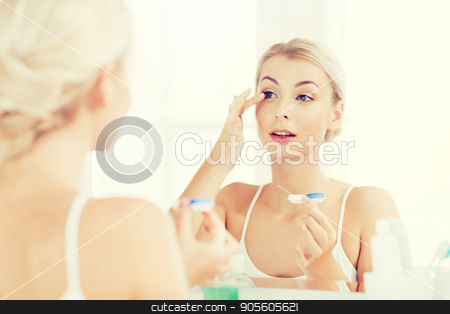 young woman putting on contact lenses at bathroom stock photo, beauty, vision, eyesight, ophthalmology and people concept - young woman putting on contact lenses at mirror in home bathroom by Syda Productions