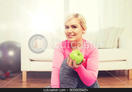 happy woman eating green apple at home stock photo, healthy eating, organic food, diet and people concept - happy woman eating green apple at home by Syda Productions