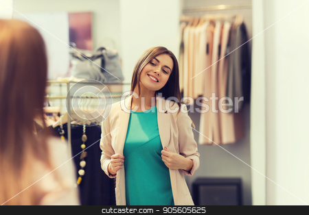 happy woman posing at mirror in clothing store stock photo, shopping, clothes, fashion, style and people concept - happy woman choosing jacket and posing at mirror in mall or clothing store by Syda Productions