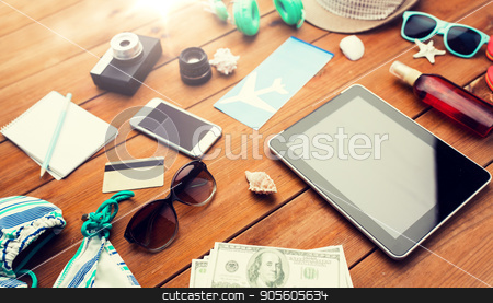 close up of tablet pc and travel stuff stock photo, vacation, tourism, technology and objects concept - close up of tablet pc computer, dollar money and travel stuff by Syda Productions