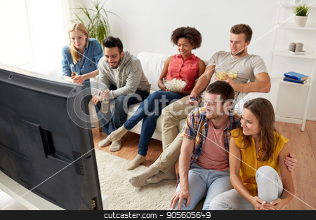 happy friends with popcorn watching tv at home stock photo, friendship, people and entertainment concept - happy friends with popcorn and beer watching tv at home by Syda Productions