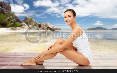 beautiful woman touching her bare legs on beach stock photo, beauty, people and bodycare concept - beautiful woman touching her smooth bare legs over exotic beach background by Syda Productions