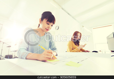 architect woman with blueprint writing at office stock photo, business, startup and people concept - creative or architect woman with blueprint writing on sticker at office by Syda Productions