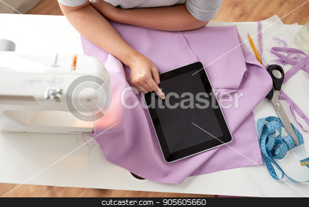 tailor with sewing machine, tablet pc and fabric stock photo, people, needlework, technology and tailoring concept - tailor woman with sewing machine, tablet pc and fabric by Syda Productions