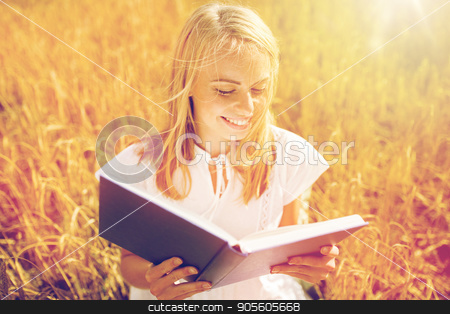 smiling young woman reading book on cereal field stock photo, country, summer holidays, literature and people concept - smiling young woman in white dress reading book on cereal field by Syda Productions