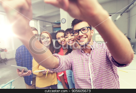 creative business team taking selfie at office stock photo, business, technology, startup and people concept - happy international creative business team taking selfie at office by Syda Productions