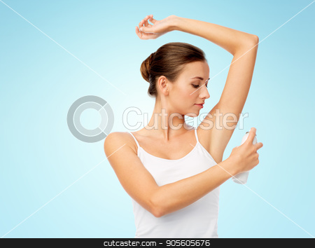 woman with antiperspirant deodorant over blue stock photo, hygiene, bodycare and people concept - beautiful young woman applying antiperspirant or spray deodorant over blue background by Syda Productions