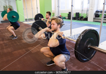 group of men training with barbells in gym stock photo, fitness, sport and people concept - men with barbells doing squats at group training in gym by Syda Productions