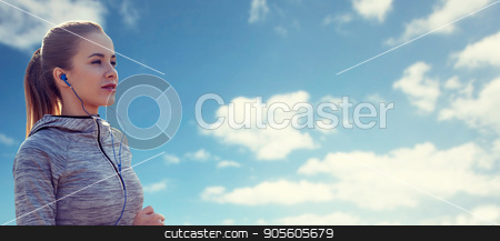 happy woman with earphones running over blue sky stock photo, fitness, sport, people, technology and lifestyle concept - happy woman running and listening to music in earphones over blue sky and clouds background by Syda Productions